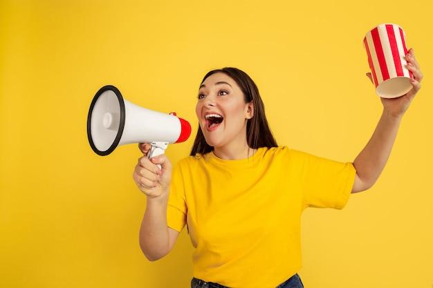 Chiamando con la bocca aperta e popcorn. donna caucasica sulla parete gialla. bellissima modella bruna femminile in stile casual. concetto di emozioni umane, espressione facciale, vendite, annuncio, copyspace. Foto Gratuite