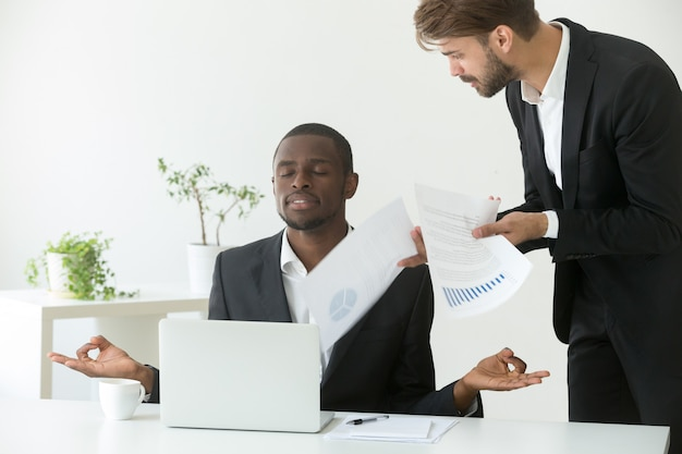 Calm african-american businessman practicing yoga at work ignoring angry boss Free Photo