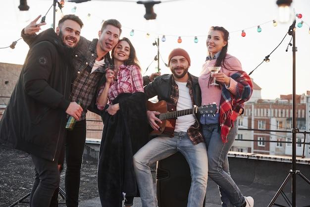 Спокойный и веселый. вечеринка на крыше. пять симпатичных друзей, которые позируют для картины с алкоголем и гитарой Бесплатные Фотографии