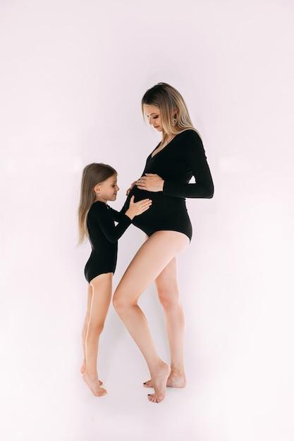 Calma madre incinta a piedi nudi in piedi con sua figlia in tute nere simili a maniche lunghe. Foto Gratuite