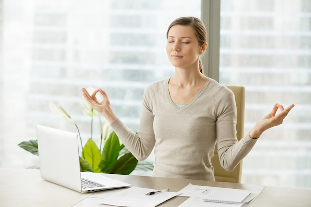 Calm businesswoman relaxing with breath gymnastics Free Photo