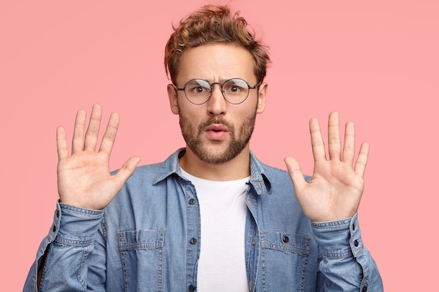 Calm down, please! handsome unshaven caucasian man keeps palms in front Free Photo