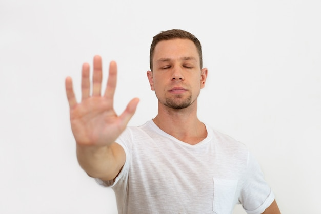 Calm handsome young man with closed eyes making stop gesture Free Photo