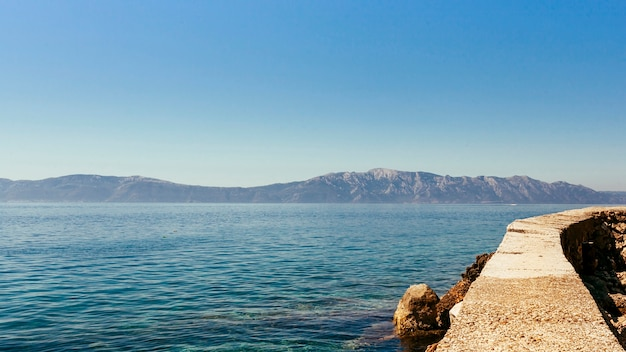 Calm idyllic sea with mountain and clear blue sky Free Photo