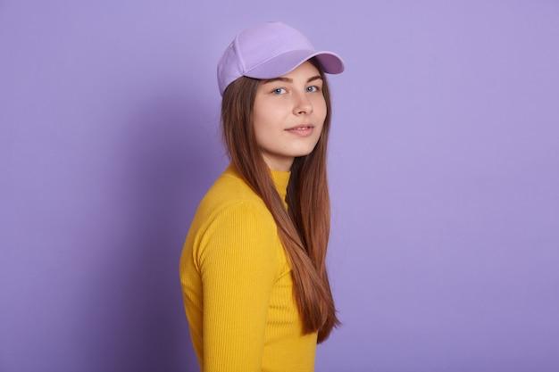 Calm lady dresses casual attire and baseball cap, posing sideways Free Photo