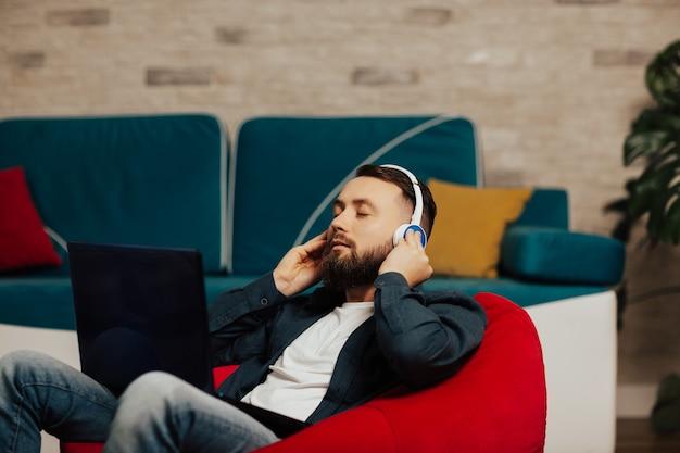 居間の赤い肘掛け椅子に座っている目を閉じた穏やかな男は、ヘッドホンをつけて膝の上にラップトップを持ち、お気に入りのトラックを聴きます。 Premium写真