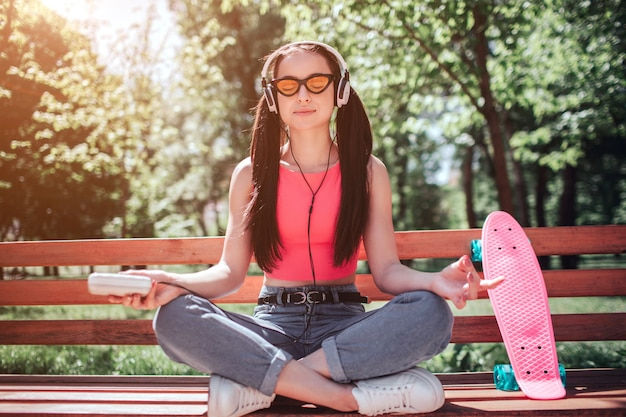 Calm and relaxed girl is meditating. she has crossed her legs and listening to music. girl is doing meditation on bench. there is a pink skate as well. Premium Photo