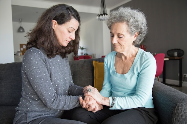 Calm senior woman and her daughter sitting and holding hands Free Photo
