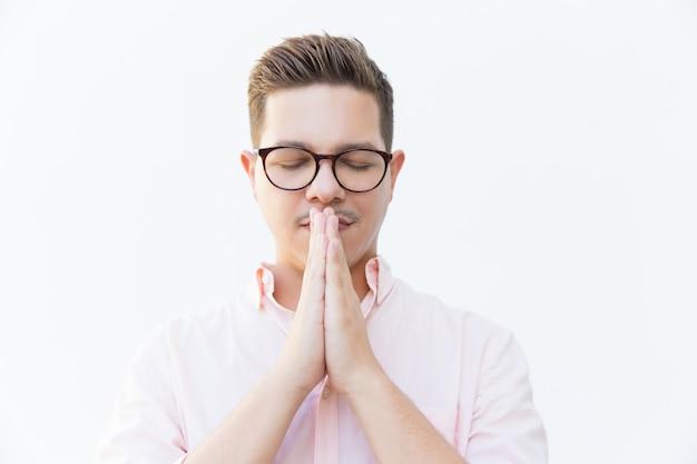 Calm serene guy in eyewear praying with closed eyes Free Photo