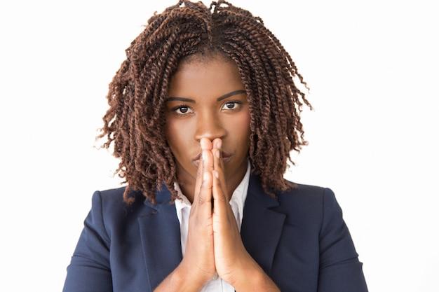 Calm serious female making pray gesture Free Photo