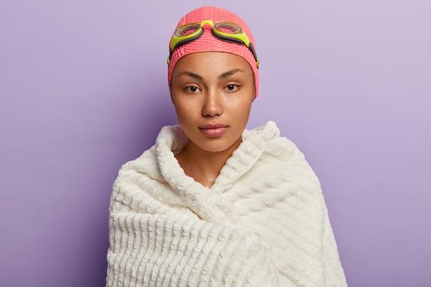 Спокойный серьезный пловец вытирается белым мягким полотенцем, согревается после плавания на спине, носит очки и шапочку для плавания, улучшает навыки, имеет влажную кожу, изолирован от фиолетовой стены, поддерживает форму Бесплатные Фотографии