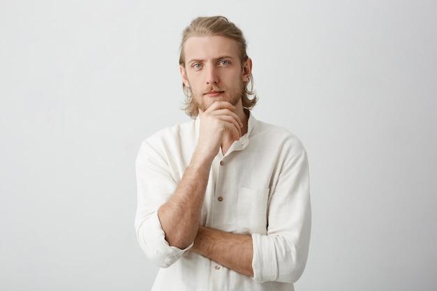 あごに手を握って、公正な髪を持つ穏やかな成功したヨーロッパのひげを生やした男性 無料写真