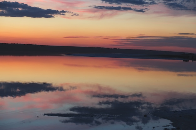 Спокойный закат с отражениями облаков в озере. Premium Фотографии