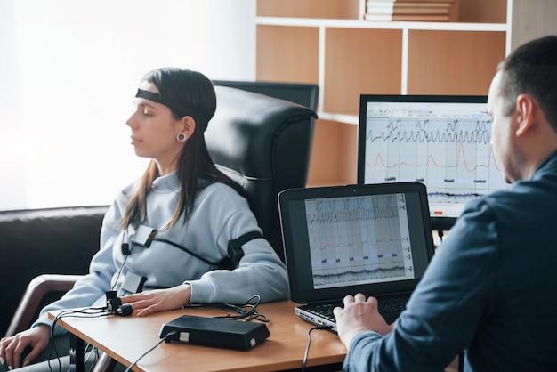 Donna calma. la ragazza passa la macchina della verità in ufficio. fare domande. test del poligrafo Foto Gratuite