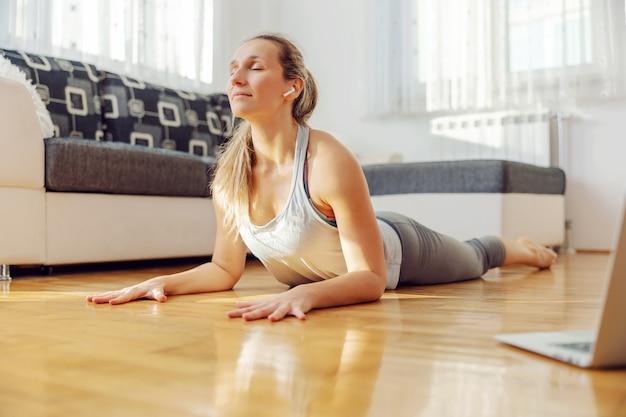 Calm, yogi woman in cobra yoga pose following online lecture at home. Premium Photo