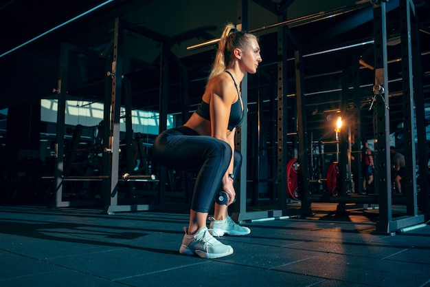 Calm. young muscular caucasian woman practicing in gym with the weights. athletic female model doing strength exercises, training her upper, lower body. wellness, healthy lifestyle, bodybuilding. Free Photo