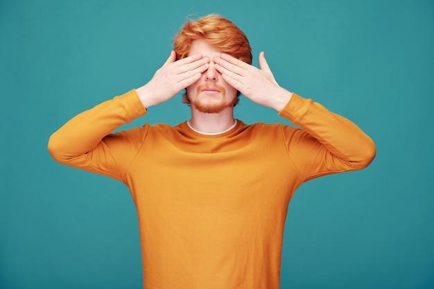 Спокойный молодой рыжий мужчина с бородой, закрывая глаза руками в ожидании удивления Premium Фотографии