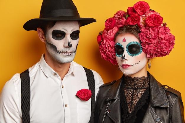 Спокойная молодая женщина и мужчина в макияже черепа, женщина в красивом цветочном венке, одетая в праздничные костюмы на хэллоуин, держат глаза закрытыми, изолированные на желтом фоне студии. Бесплатные Фотографии
