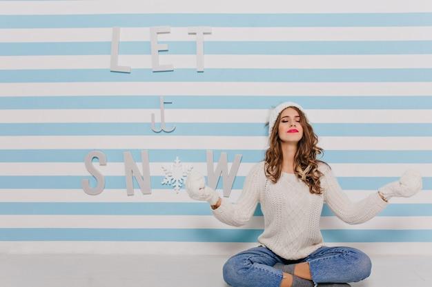 蓮華座に座って、ヨーロッパからの穏やかな若い女性がポーズします。冬のセーターの女の子と青い壁に明るい口紅 無料写真