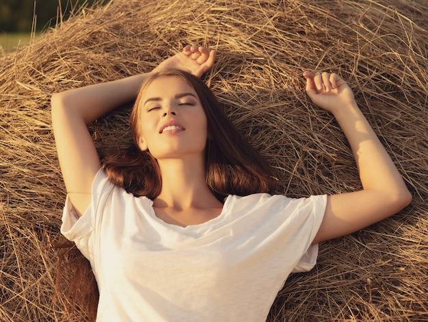 穏やかな若い女性は干し草の山でリラックスしています。美しい穏やかな女の子は自然にあります。長い茶色の髪の幸せなブルネットの少女。自然のかわいいモデルの肖像画。リラックスした夏の時間。 無料写真