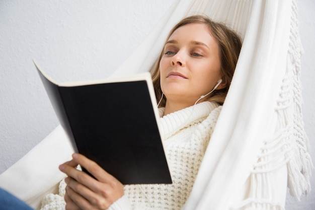 Calm young woman reading book and listening to music Free Photo