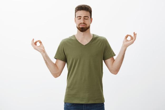 Успокоение и снятие стресса с помощью медитации. решительный и расслабленный привлекательный бородатый парень в оливковой футболке держится за руки в позе лотоса, достигая нирваны, закрывает глаза и радостно улыбается Бесплатные Фотографии