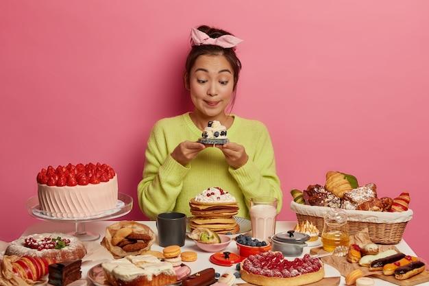칼로리 음식, 유혹 및 잃어버린 체중 개념. 사랑스러운 외모를 가진 한국 소녀는 식욕이 좋은 달콤한 머핀을보고 맛있는 간식을 즐기고 분홍색 배경에 포즈를 취합니다. 무료 사진