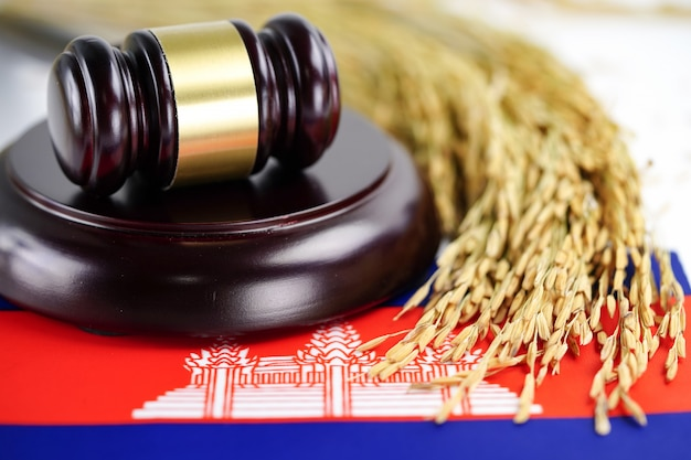 Cambodia flag and judge hammer with gold grain from agriculture farm. Premium Photo