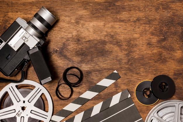 フィルムリール付きビデオカメラ。カチンコ木製の背景上のフィルムストライプ Premium写真