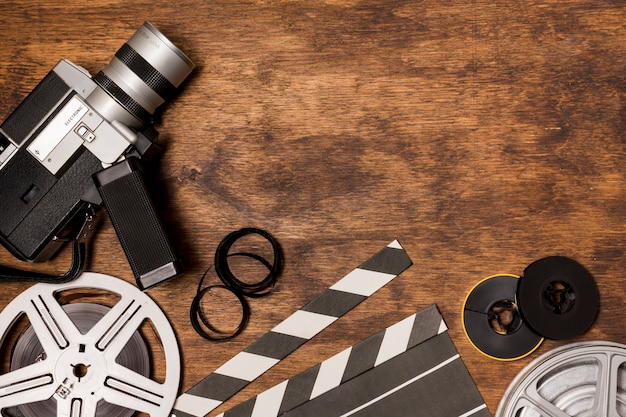 Camcorder camera with film reel; clapperboard; film stripe on wooden background Free Photo