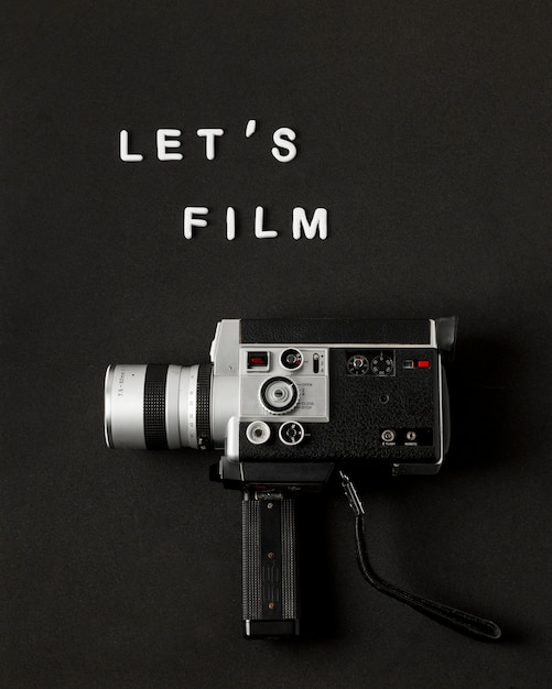 Camcorder camera with text let's film on black background Free Photo