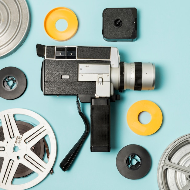 Camcorder and film reels cases on blue background Free Photo