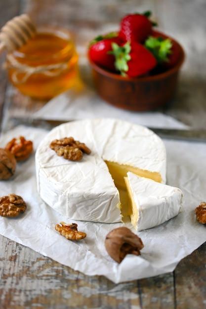 Сыр камамбер с клубникой, медом и орехами. Premium Фотографии