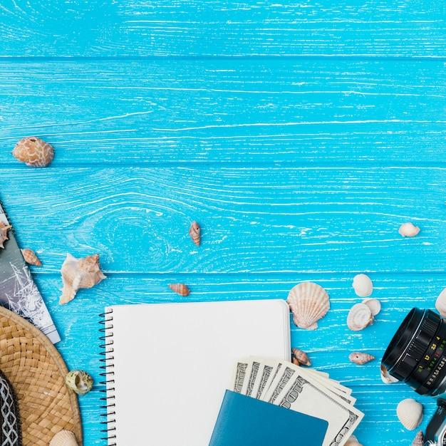 Camera among seashells and money with notepad Free Photo