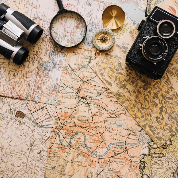 Camera and compass near magnifying glass and binoculars Free Photo