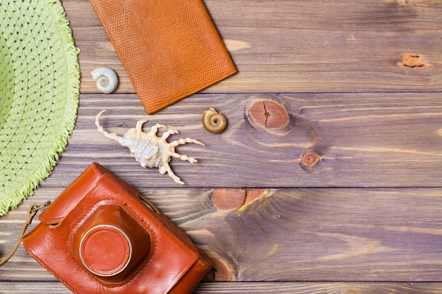 Camera in a case, passport, hat and seashells on a wooden background Premium Photo