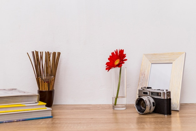 Camera flower photo frame and books on table Free Photo
