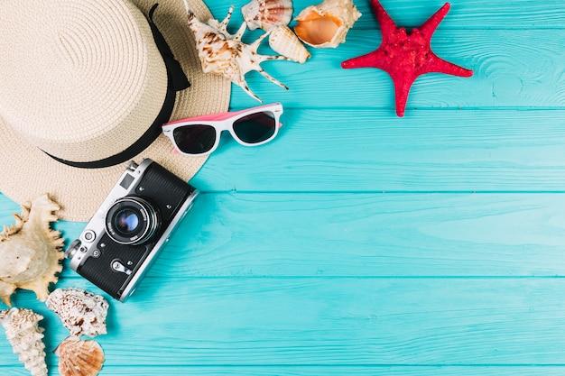 Camera and hat near sunglasses and seashells Free Photo