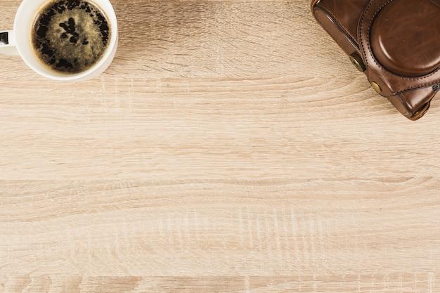 Камера в сумке и кофейной чашке на деревянном столе Бесплатные Фотографии