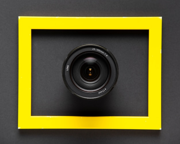 Camera lenses inside a yellow frame on black background Free Photo