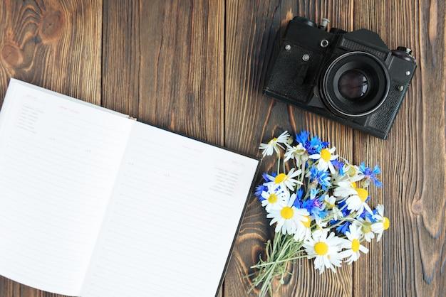 어두운 나무 배경에 카메라, 노트북, 휴대 전화 및 필드 꽃. 프리랜서. 사진의 수입. 프리미엄 사진