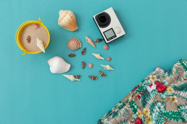 Camera, seashell, sand,beach pants,dragon fruit and smartphone over blue Premium Photo