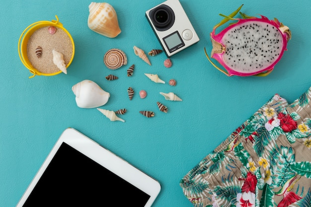 Camera, seashell, sand,beach pants,dragon fruit and smartphone over blue Premium Photo