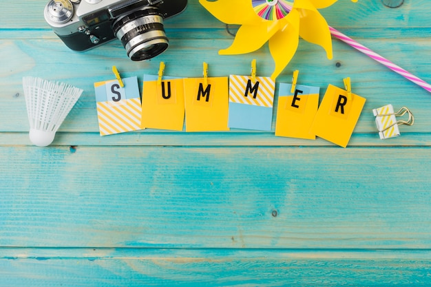 Camera; shuttlecock; pinwheel and summer with clothespin on wooden desk Free Photo
