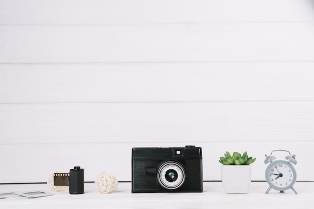 Camera with clock,plant and negatives Free Photo