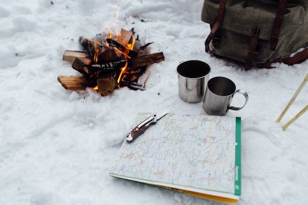 Camping. bonfire with two mugs, map and knife on snow Free Photo