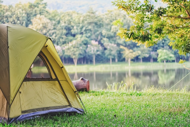 Premium Photo | Camping green tent in forest near lake