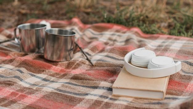 Кемпинг на природе с книгой и кружками для горячих напитков Бесплатные Фотографии