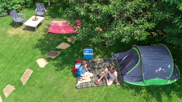Campsite aerial view from above, mother and daughter having fun, tent and camping equipment under tree, family vacation in camp outdoors concept Premium Photo