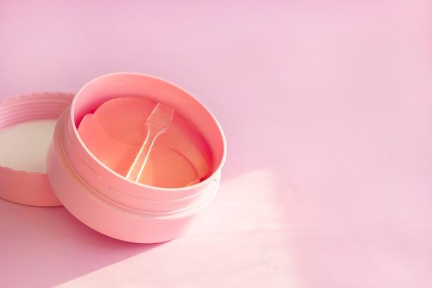 Может гидрогелевая косметическая накладка для ухода за кожей на розовом фоне. Premium Фотографии